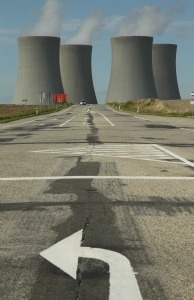 A traffic arrow points on a street that leads by the four cooling towers of the Temelin nuclear power plant.