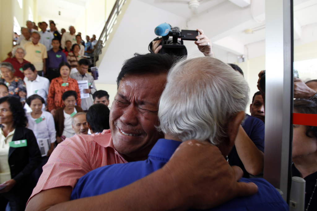 Cambodian former Khmer Rouge servitors, Soum Rithy, left, and Chum Mey, right, embrace each other after the verdicts were announced, at the U.N.-backed war crimes tribunal in Phnom Penh, Cambodia, Thurdday, Aug. 7, 2014. Three and a half decades after the genocidal rule of Cambodia's Khmer Rouge ended, the tribunal on Thursday sentenced two top leaders of the former regime to life in prison on war crimes charges for their role in the country's terror period in the 1970s. (AP Photo/Heng Sinith)