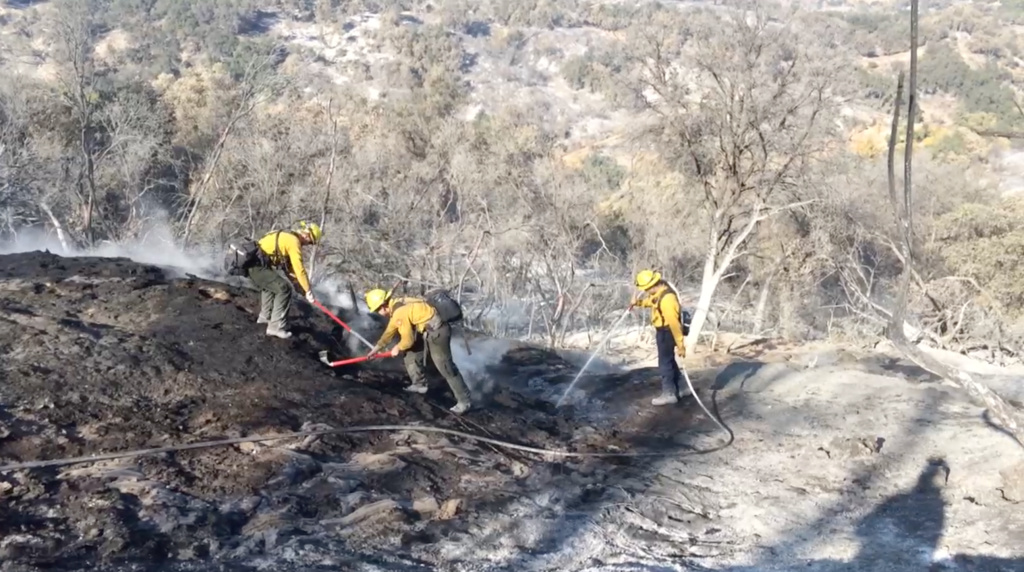 Fire crews use spades and shovels to combat an oil fire in the hills above the Ojai Valley. The naturally-occurring crude was set ablaze by the Thomas Fire earlier this month. The oil seeps are still on fire in more than 100 places, Hodge said.