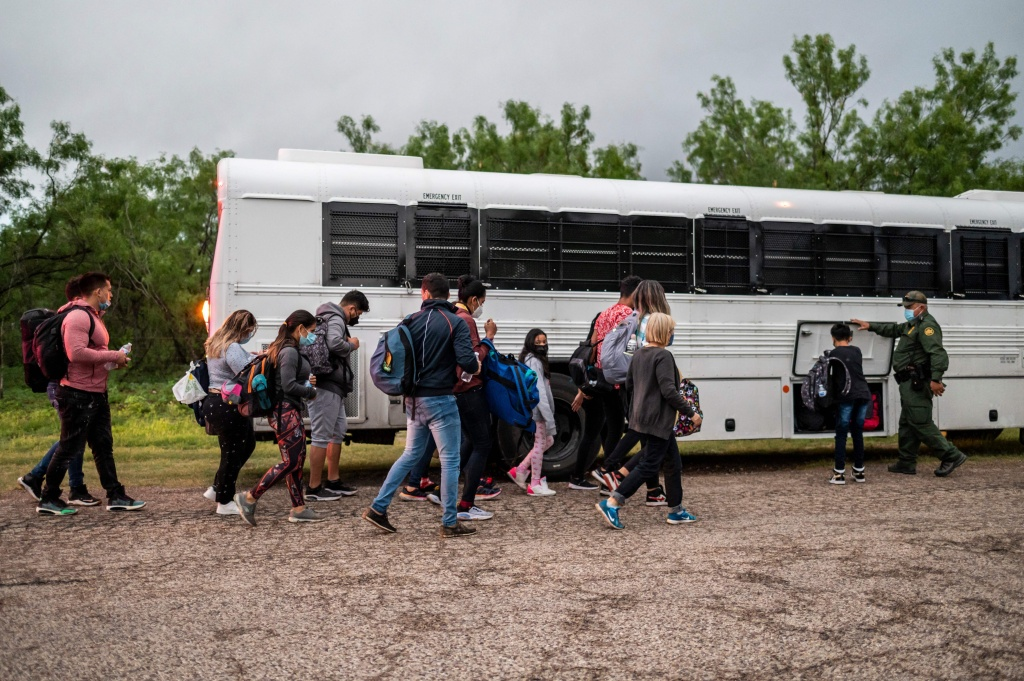 Migrants make their way toward a bus after being apprehended near the border between Mexico and the United States in Del Rio, Texas, on Sunday.