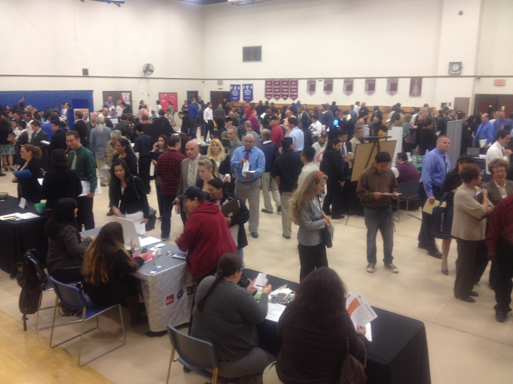People fill a basketball gym in Fountain Valley to apply for 600 job openings with 33 companies.