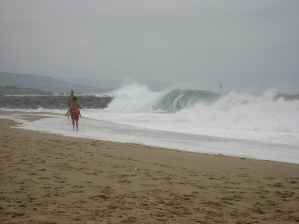 """A lifeguard runs toward the jetty at """"The Wedge"""" in Newport Beach at the same time a body surfer got slammed into the rocks and was killed Friday."""