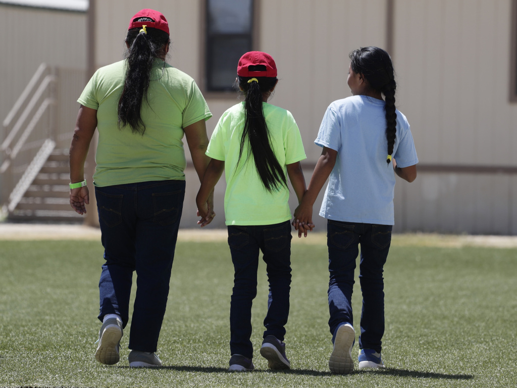 Immigrants seeking asylum hold hands as they leave a cafeteria at the ICE South Texas Family Residential Center. Independent inspectors told the judge that COVID-19 tests at the centers and the infection rates in the counties where the Texas facilities are located are cause for concern.