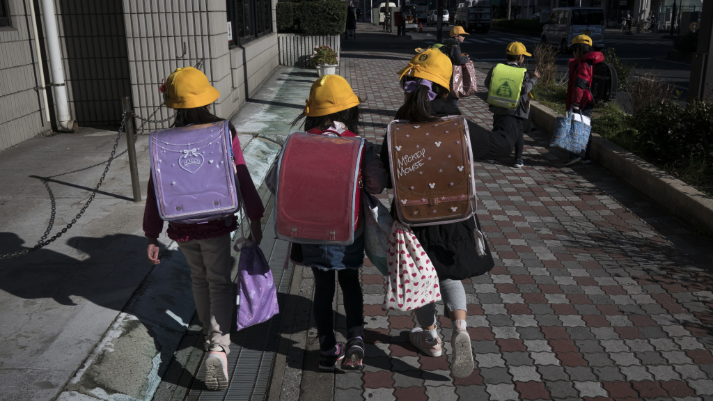Japan is asking all schools from the elementary to high school level to shut down for the next month, citing the risk of spreading the COVID-19 coronavirus. Here, elementary school students head home Thursday in Ichikawa, Japan.