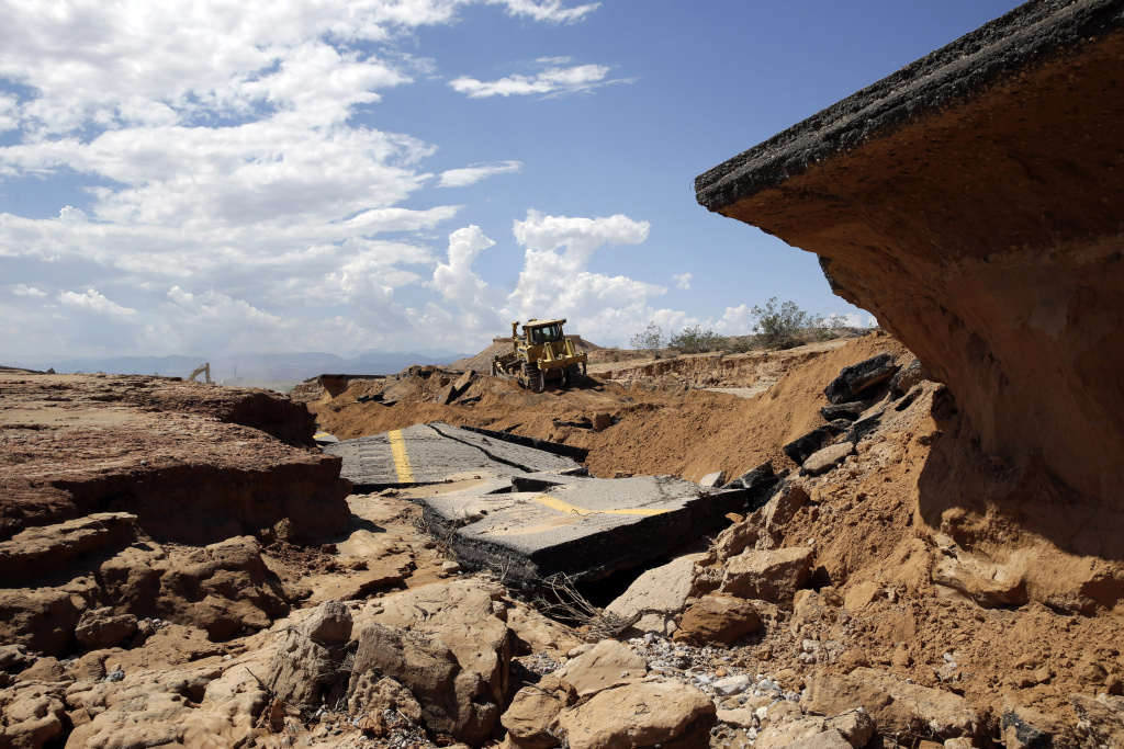 A bulldozer works on a flood damaged section of Interstate 15, Tuesday, Sept. 9, 2014, near Moapa, Nev. Flood damage caused the closure of the interstate which is the main road between Las Vegas and Salt Lake City.
