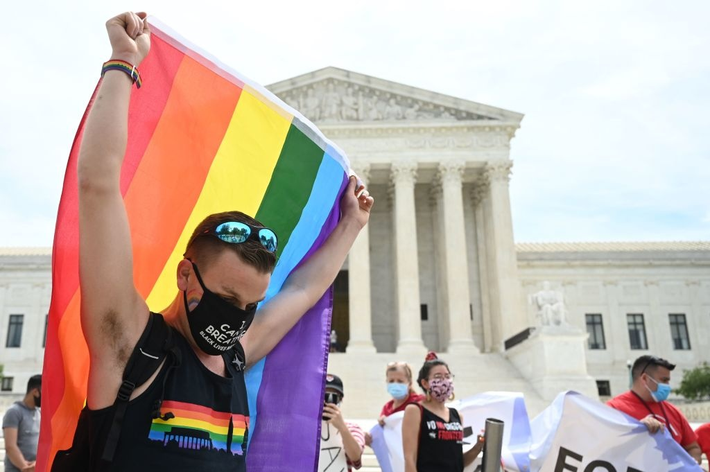 A man waves a rainbow flag in front of the US Supreme Court that released a decision that says federal law protects LGBTQ workers from discrimination on June 15, 2020 in Washington,DC.