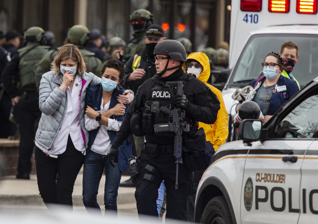 Healthcare workers walk out of a King Sooper's Grocery store after a gunman opened fire on March 22, 2021 in Boulder, Colorado.