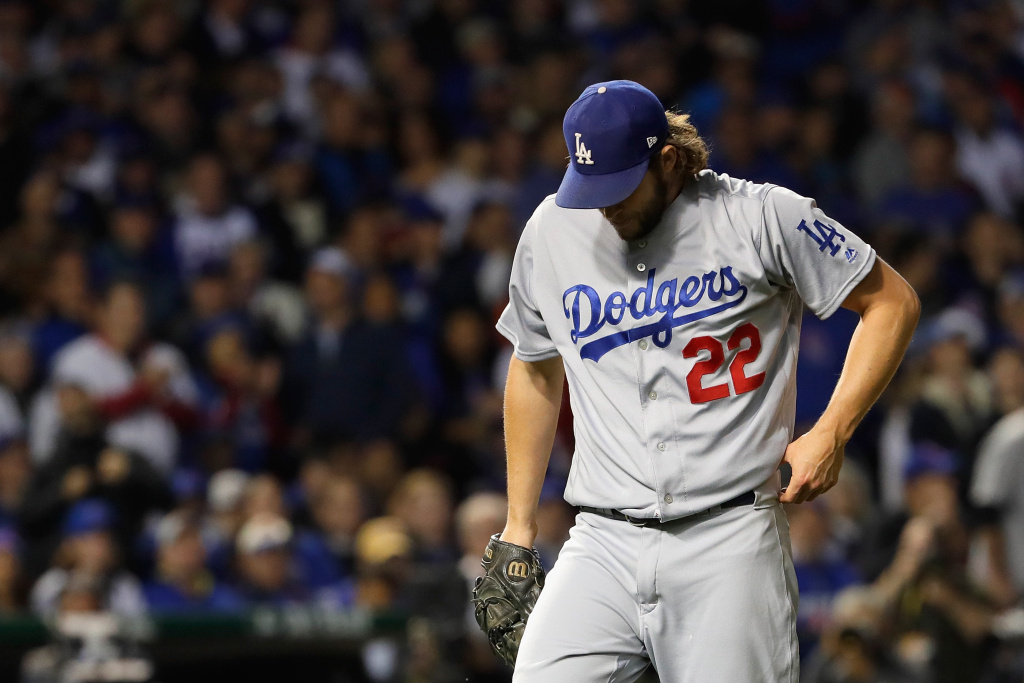 Clayton Kershaw #22 of the Los Angeles Dodgers walks back to the dugout after the first inning against the Chicago Cubs at Wrigley Field in this October 22, 2016 file photo. A settlement has been reached in a lawsuit that claimed DirecTV swapped information with Cox Communications Inc., Charter Communications Inc. and AT&T — before it acquired DirecTV — during negotiations to carry the SportsNet LA, the network owned by the Dodgers.