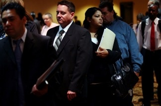 Job applicants line up for interviews at a career fair.