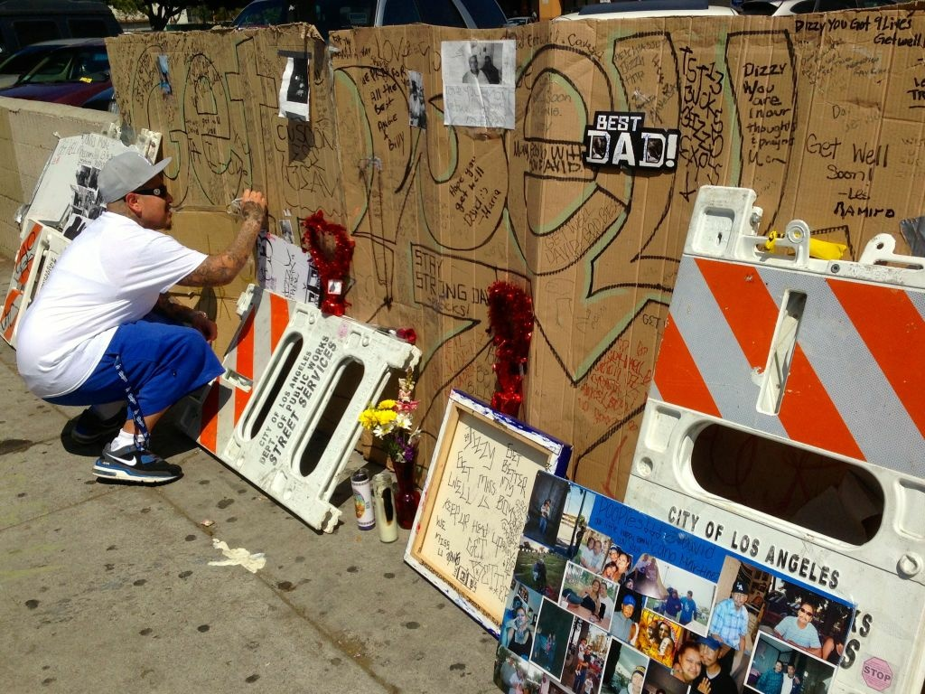 An unidentified man signs a poster at the makeshift memorial in Echo Park for David Martinez, who was shot by LAPD officers