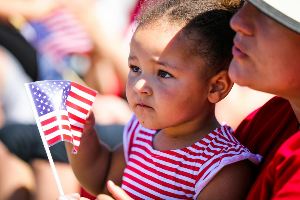 Athena Volante, 2, holds an American flag as she sits with her grandmother, Valla Burnett (R), during the 4th of July Parade in Alameda, California on Monday, July 4, 2016. / AFP / GABRIELLE LURIE        (Photo credit should read GABRIELLE LURIE/AFP/Getty Images)