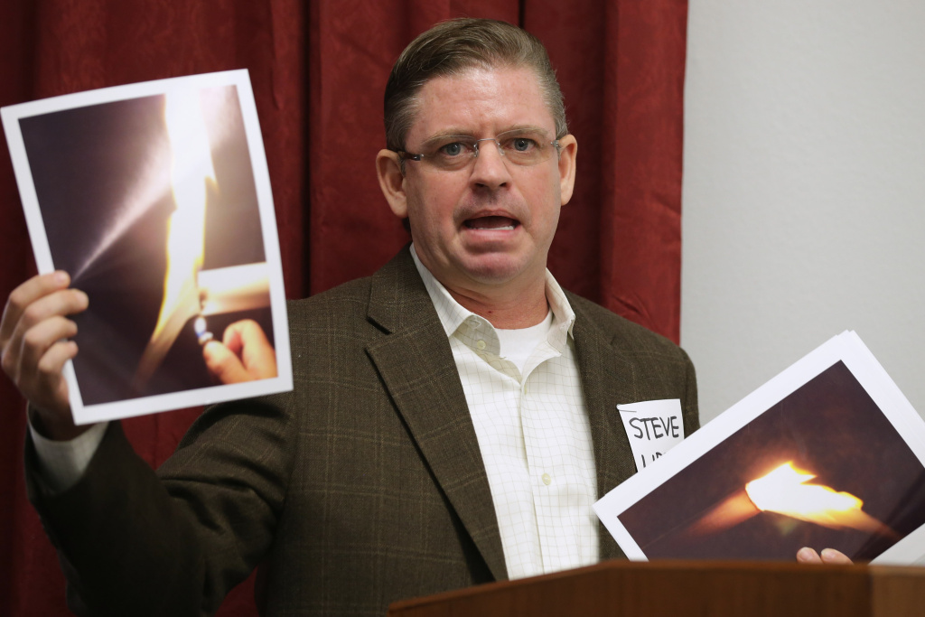 Steve Lipsky of Parker County, Texas, holds photographs of his well water burning during a briefing organized by anti-fracking groups at the Cannon House Office Building on Capitol Hill February 5, 2014 in Washington, DC. Lipsky's water well was the subject of an EPA emergency order after he says it was contaminated by oil and gas exploration. People from communities affected by underground hydraulic fracturing used to extract natural gas, or fracking, called on members of Congress, the Environmental Protection Agency and President Barack Obama to continue investigating the connection between fracking and residential water contamination.