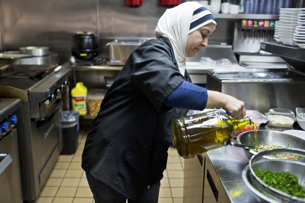 Hamsa Al Moukdad, a cook at Aleppo's kitchen, pours olive oil into a bowl to make tabbouleh.