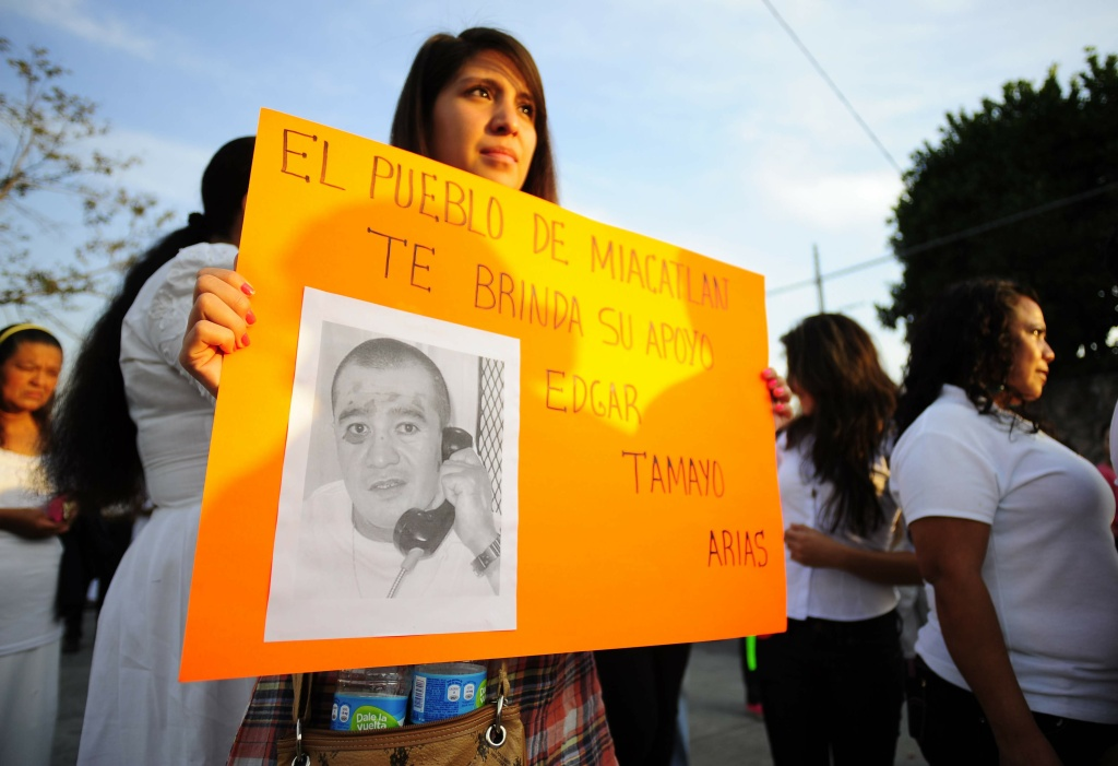 In this Jan. 19, 2014 photo, a woman holds up a sign showing a photo of Texas death-row inmate Edgar Tamayo that reads in Spanish