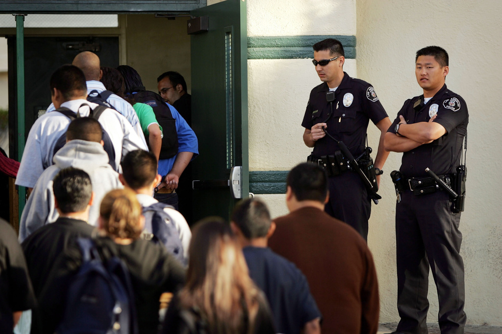 Los Angeles School Police officers watch students lining up to pass through a security check point in the aftermath of two apparent racially motivated student brawls at Thomas Jefferson High School April 21, 2005 in Los Angeles, California. The L.A. Unified School District has required all of its secondary schools to perform daily random screenings using metal detectors since an incident 20 years ago, and security has become a top concern again following the recent school shootings at Sandy Hook Elementary in Newtown, Conn.