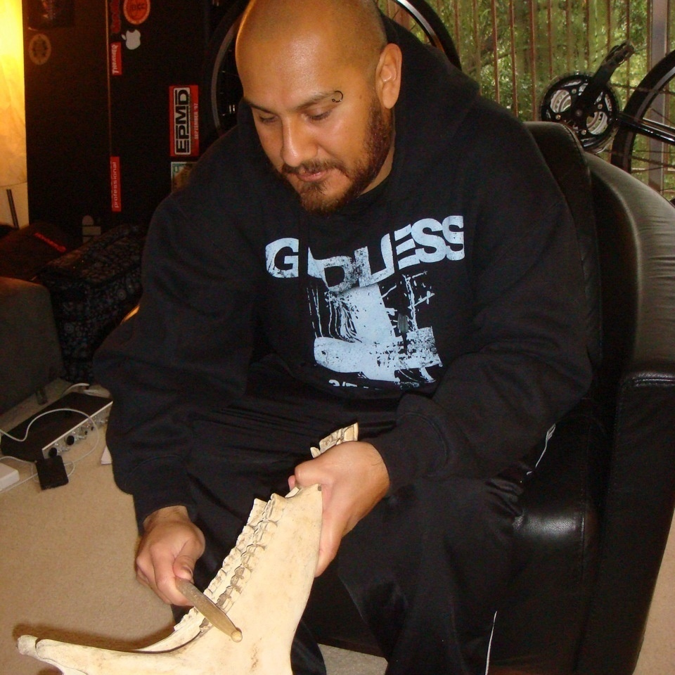 Marco Santiago plays a quijada in his home.