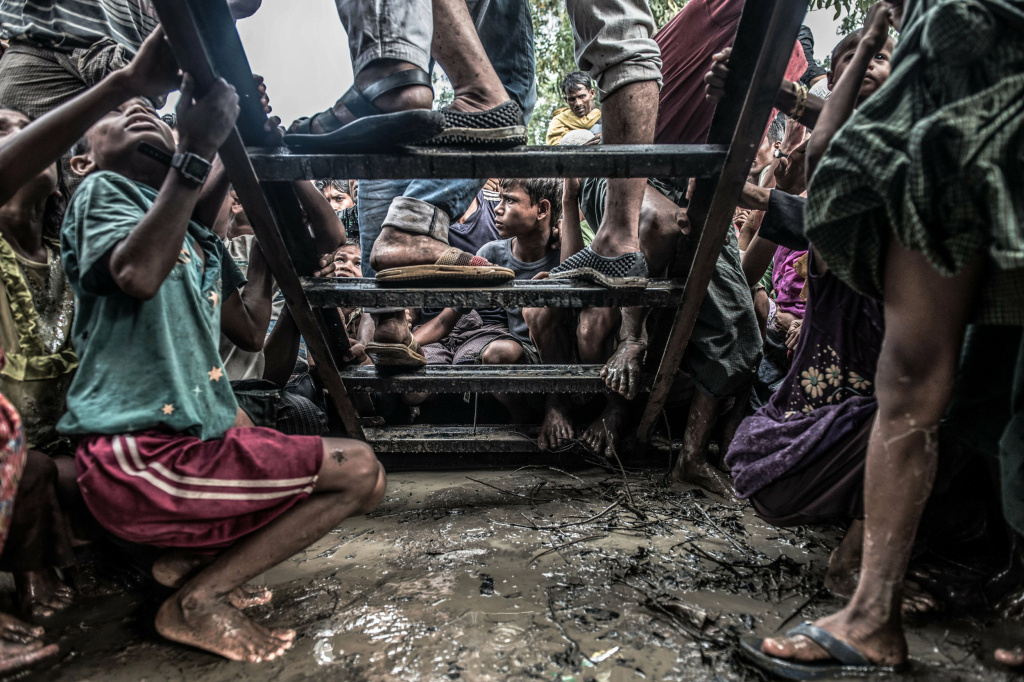 Rohingya refugees cluster around a food distribution truck in Kutupalong camp, southern Bangladesh.