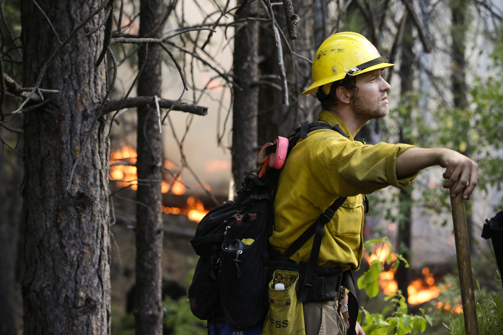 Firefighter Brandon Wenger stands along Highway 120 while monitoring a backburn during the Rim Fire near Yosemite National Park, Calif., on Tuesday, Aug. 27, 2013.