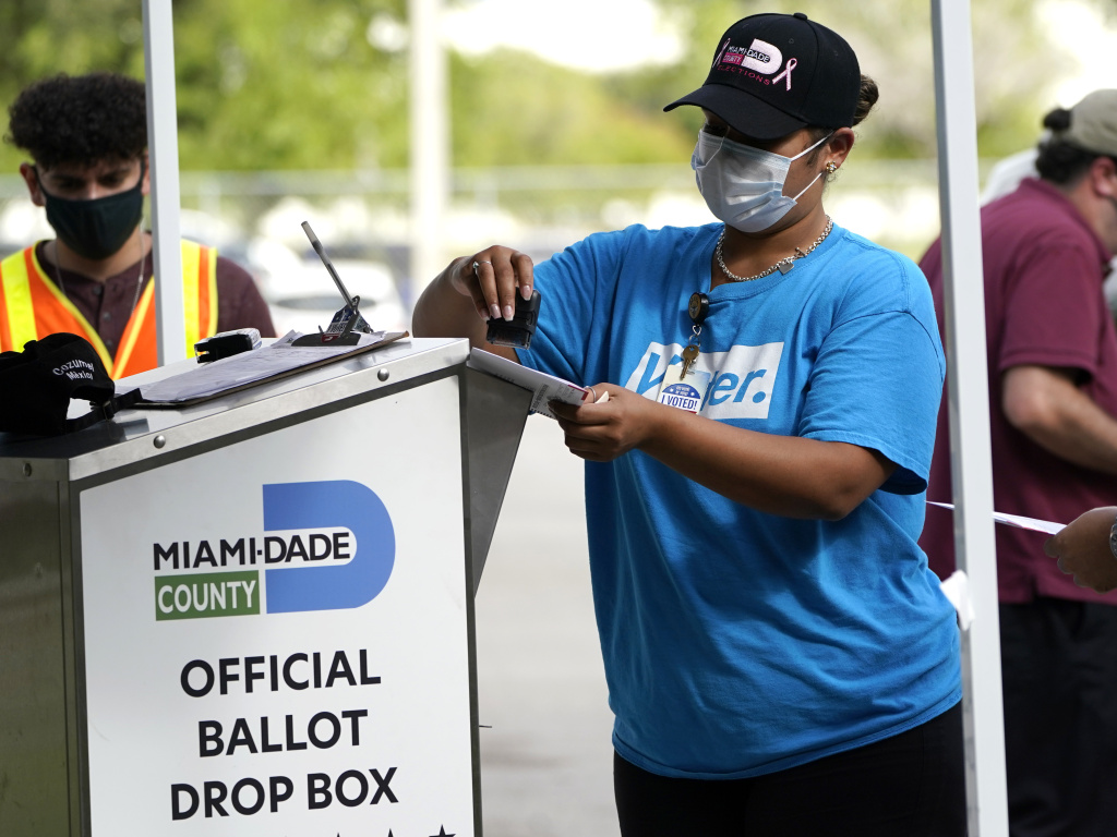 An election worker stamps a vote-by-mail ballot dropped off by a voter before placing it in an official ballot drop box at the Miami-Dade County Board of Elections in Doral, Fla., in October 2020. The Florida state Senate on Monday passed a bill that would reduce access to drop boxes.