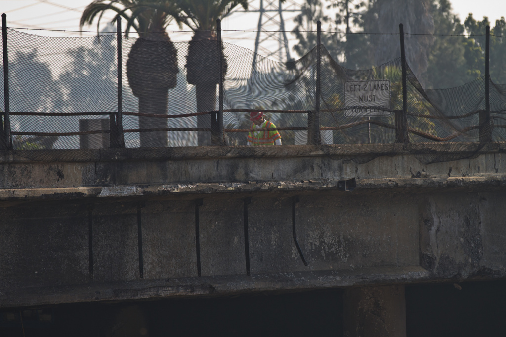 A worker inspects the burned Paramount Boulevard bridge across the 60 Freeway.