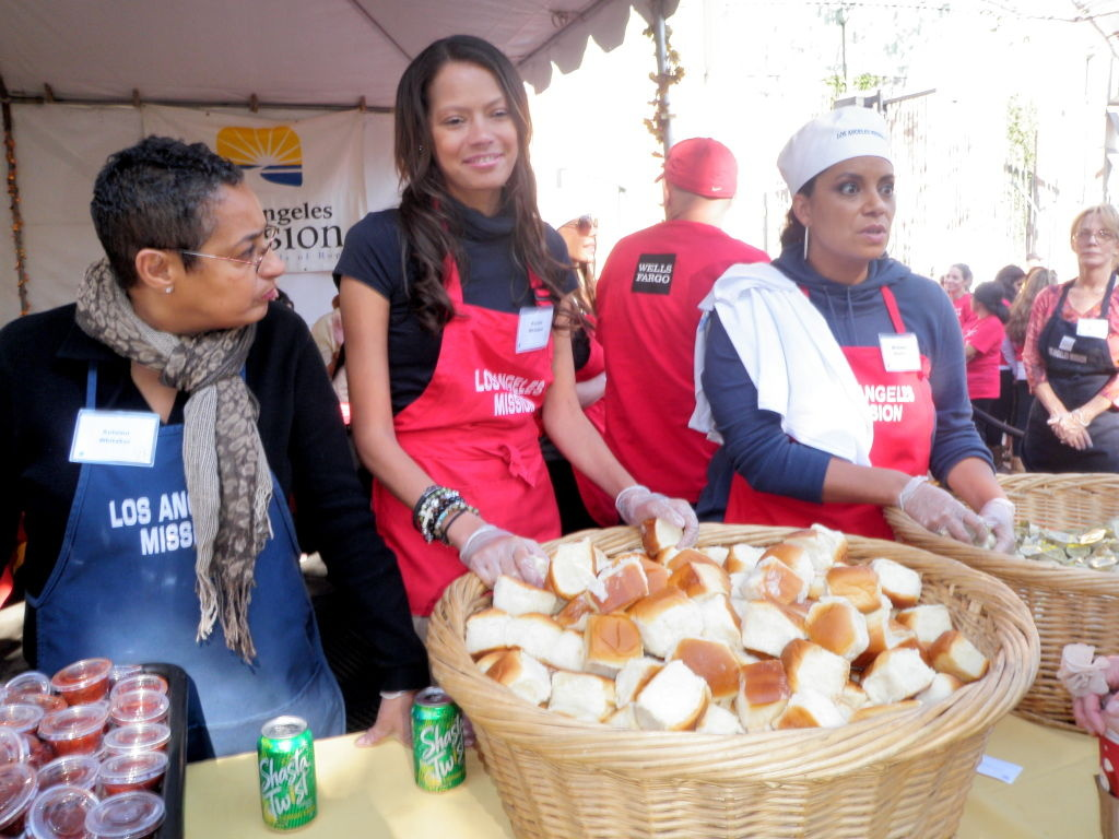Keisha Whitaker, center, volunteers distributing meals during the Los Angeles Mission pre-Thanksgiving celebration on Skid Row.