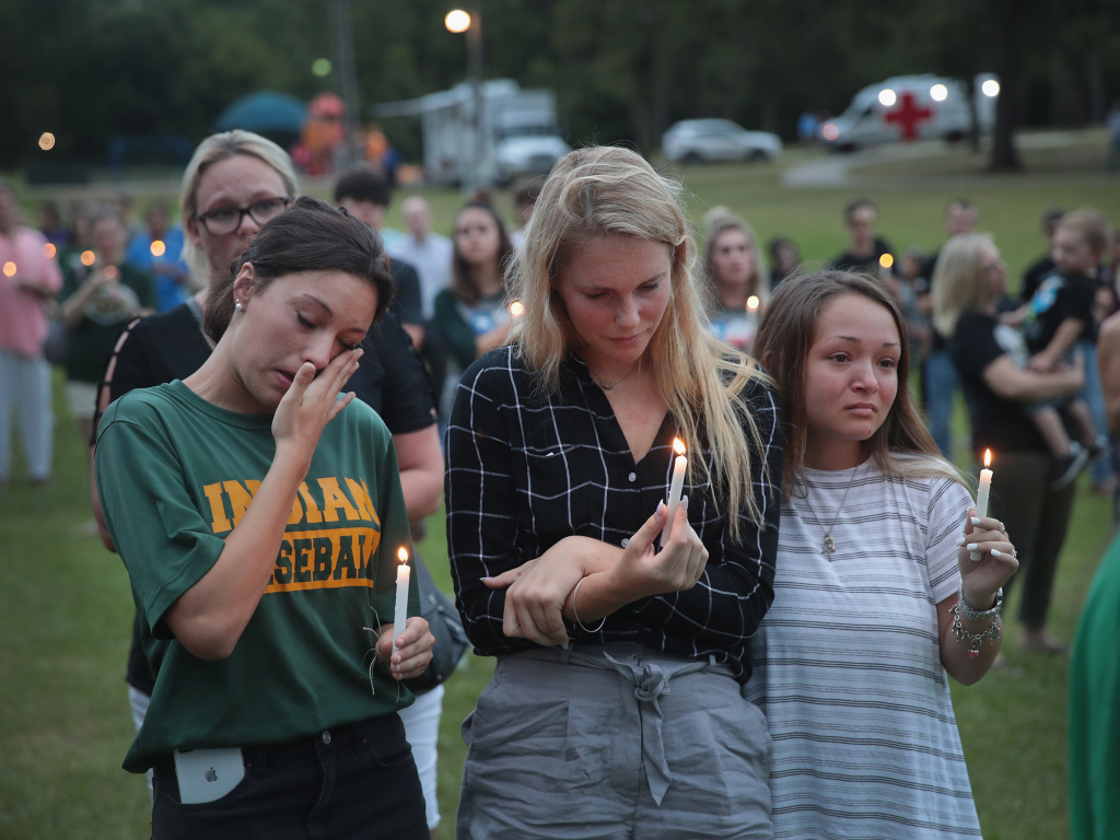 Mourners attend a prayer vigil to remember the victims of the Santa Fe High School shooting on Sunday in nearby League City, Texas. On Friday, a student allegedly entered the school with two guns and opened fire, killing 10 people.