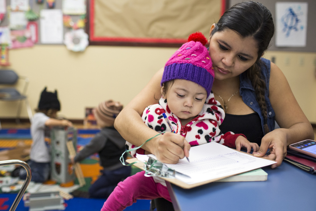 Francis Amaya and her 22-month-old daughter, Amy Cardosa, sign in before a parent training put on by the Children's Bureau at the Pico Union Branch Library on Friday morning, May 20, 2016. Children's Bureau CEO Alex Morales says funding for infant and toddler care and preschool is limited.