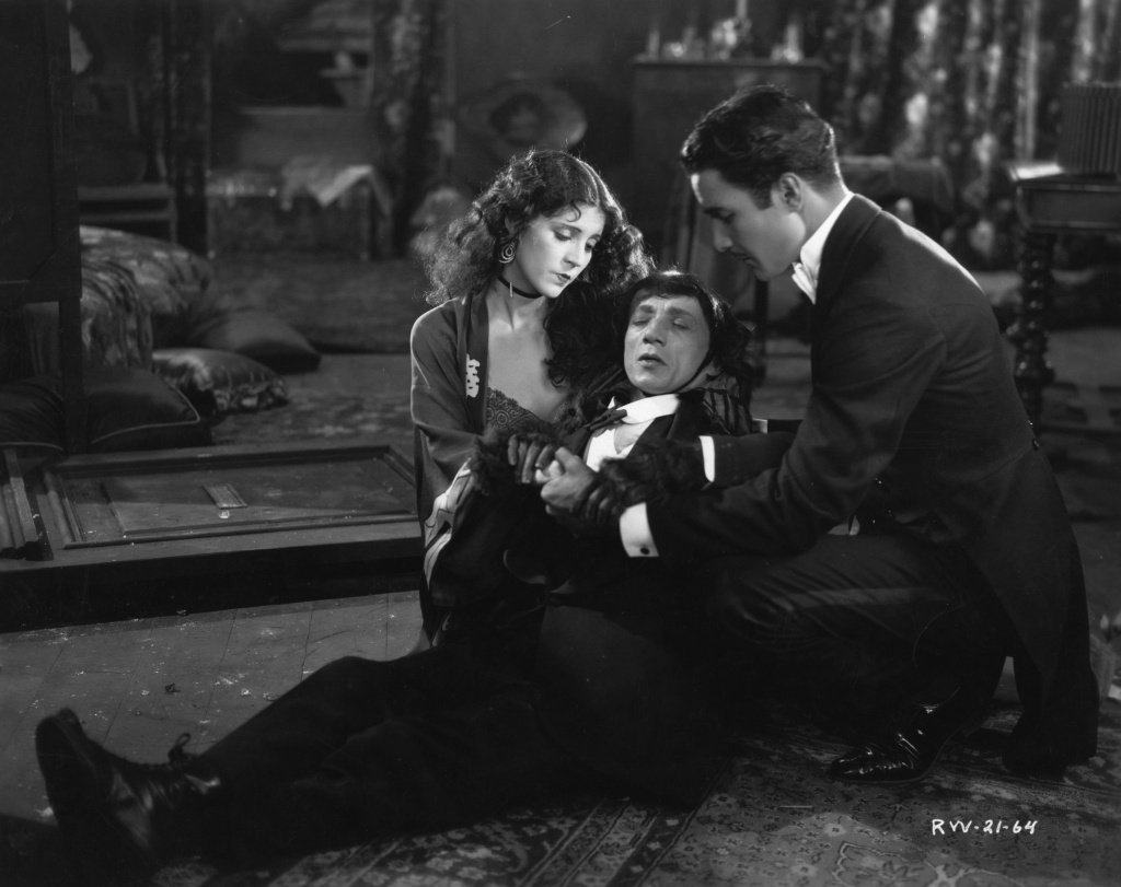 Actors Olive Borden and Don Alvarado support a stricken Jacques Lerner in a scene from the 1927 movie romance