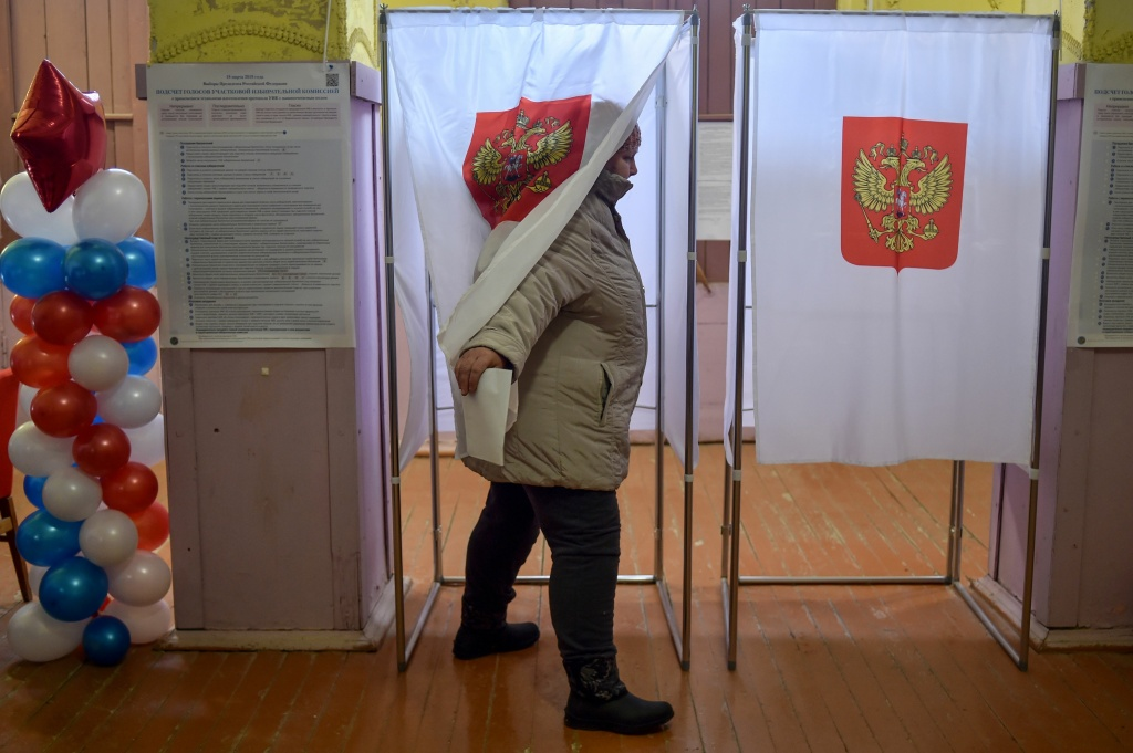 A woman walks out of a voting booth at a polling station during Russia's presidential election in the village of Borok on March 18, 2018.