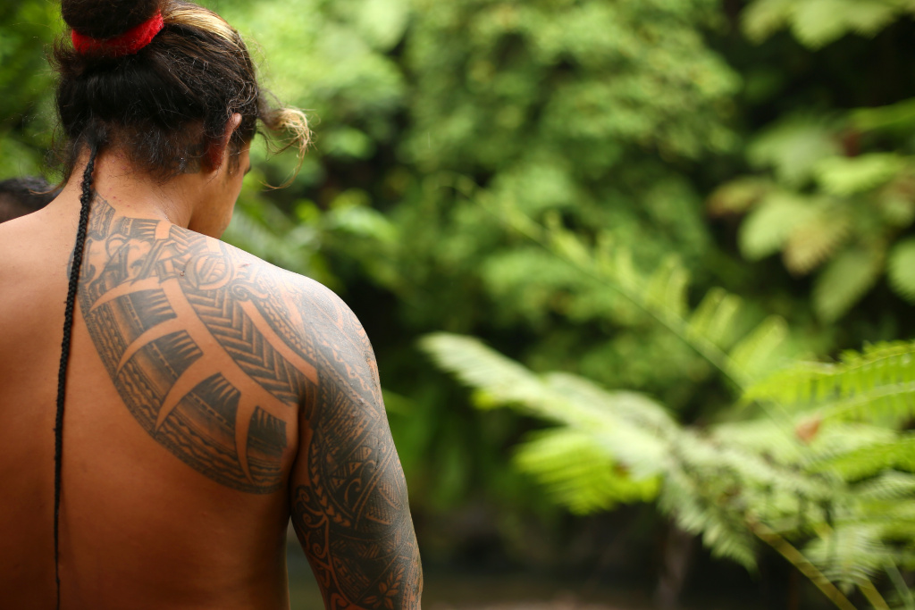 The tattoos of a local man are seen as he walks to the Togitogiga Waterfall in the O le Pupu-Pue National Park on September 12, 2015 near Poutasi, Samoa.