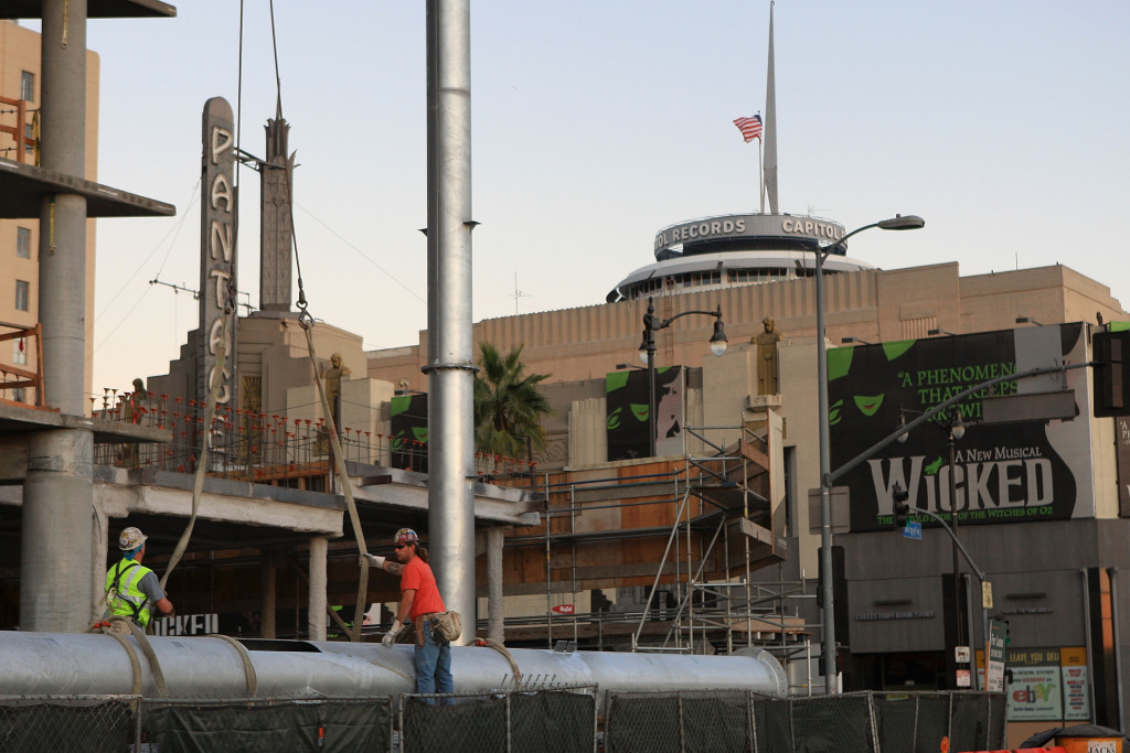 The Pantages Theater and the cylindrically-shaped Capitol Records building are seen behind workers during the construction of the W hotel complex. New zoning laws aim to facilitate development of residential and commercial districts.