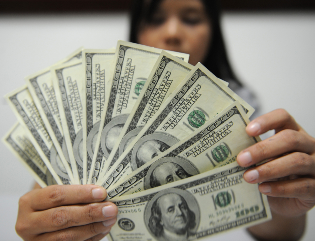 A bank employee displays US dollar notes in Manila on August 3, 2011.