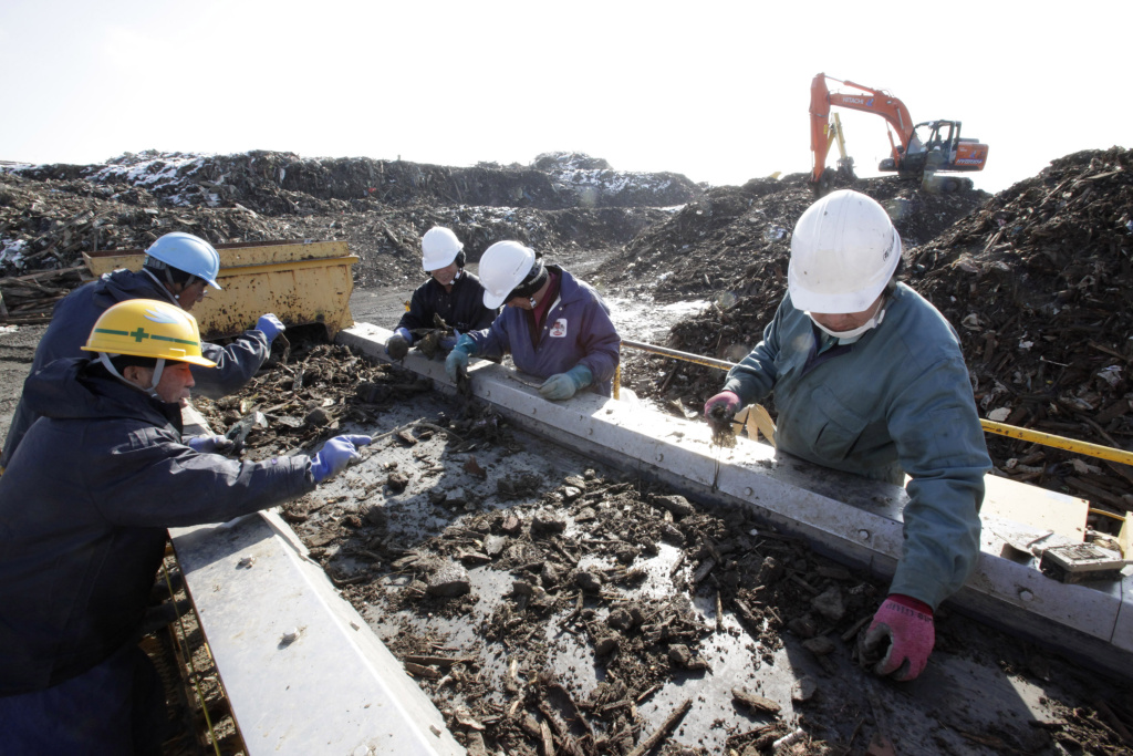In this photo taken Thursday, March 1, 2012, workers sort debris in Minamisanriku nearly a year after the March 11 tsunami hit the northeastern Japanese town. The Japanese government aims to finish the entire tsunami cleanup process over the next two years.