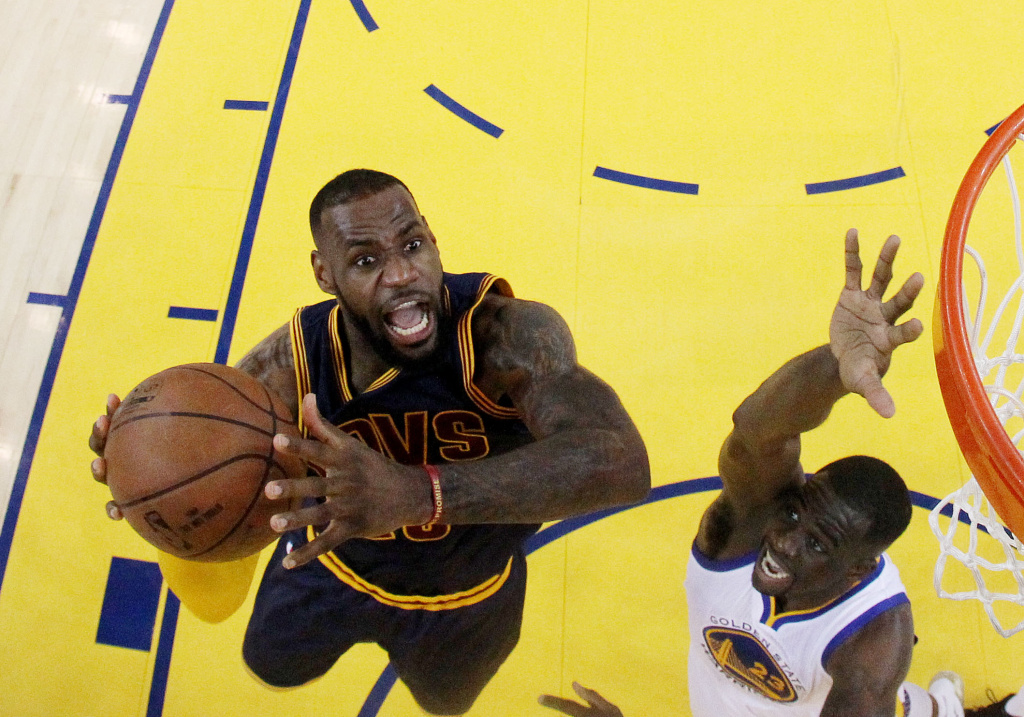 LeBron James #23 of the Cleveland Cavaliers goes up against Draymond Green #23 of the Golden State Warriors in the first half during Game Five of the 2015 NBA Finals on June 14, 2015 in Oakland, California.