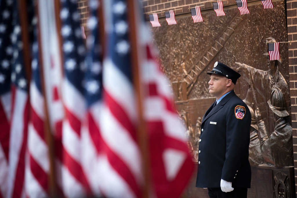 A New York City firefighter stands outside FDNY Engine 10, Ladder 10 station near the September 11 Memorial site and One World Trade Center, September 11, 2016 in New York City.