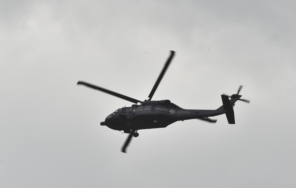A federal police Black Hawk helicopter flies over a house at the end of a tunnel through which drug lord Joaquin
