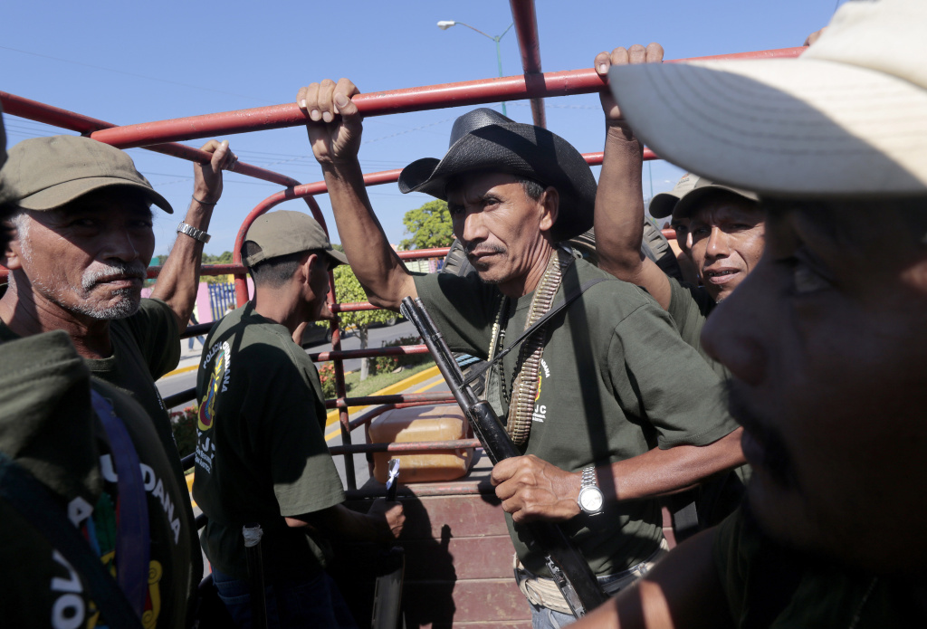 Armed residents take part in a march for the first anniversary of the citizen's vigilante groups, in Ayutla de los Libres, on January 5, 2014, in the southeastern state of Guerrero, Mexico. Hundreds of civilians armed with rifles, pistols and machetes decided to provide security for the communities of Guerrero, creating a vigilante force, following robberies, kidnappings and murder by gangs. Guerrero, home to the Pacific resort town of Acapulco, has been one of the states hardest hit by Mexico's drug violence, which has left more than 70,000 people killed across the country since 2006.