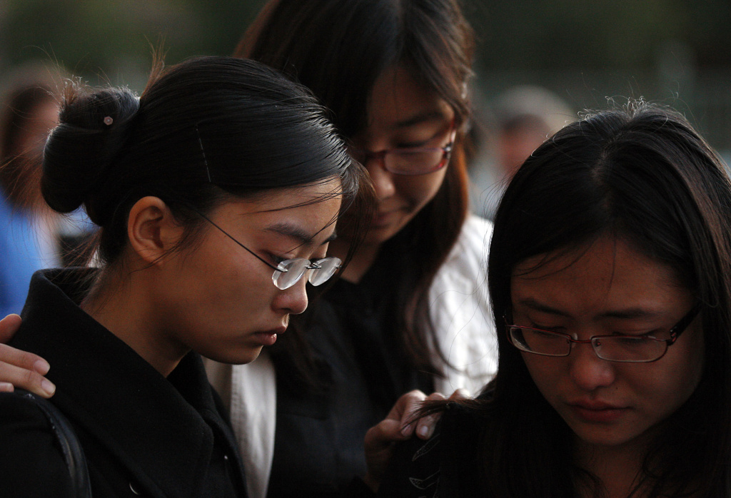 USC students stand in silence outside the Shrine Auditorium following a memorial service April 18, 2012, for Ying Wu and Ming Qu, a pair of foreign students studying engineering who were fatally shot as they sat in a parked car near campus.