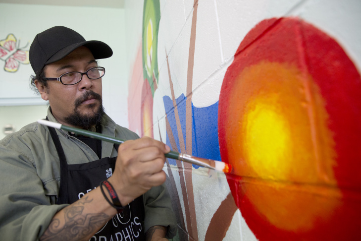 When some girls want to take a break from the mural, Nery Gabriel Lemus, a teaching artist with the Armory Center for the Arts, gives them tips on drawing.