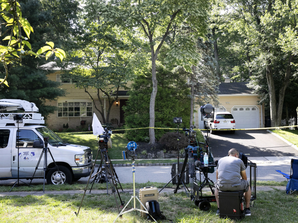 News media set up in front of the home of U.S. District Judge Esther Salas on Monday in North Brunswick, N.J. A gunman posing as a delivery person shot and killed Salas' 20-year-old son Sunday evening. investigators say there could be a connection between this attack and one in California earlier this month.