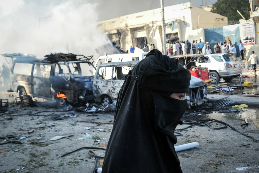 A woman walks by wreckages of vehicles after a truck bomb exploded in the center of Mogadishu on October 15, 2017.
