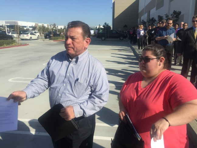 Willie Ortega and his daughter Stephanie hand in their resumes at the Virgin Galactic jobs fair