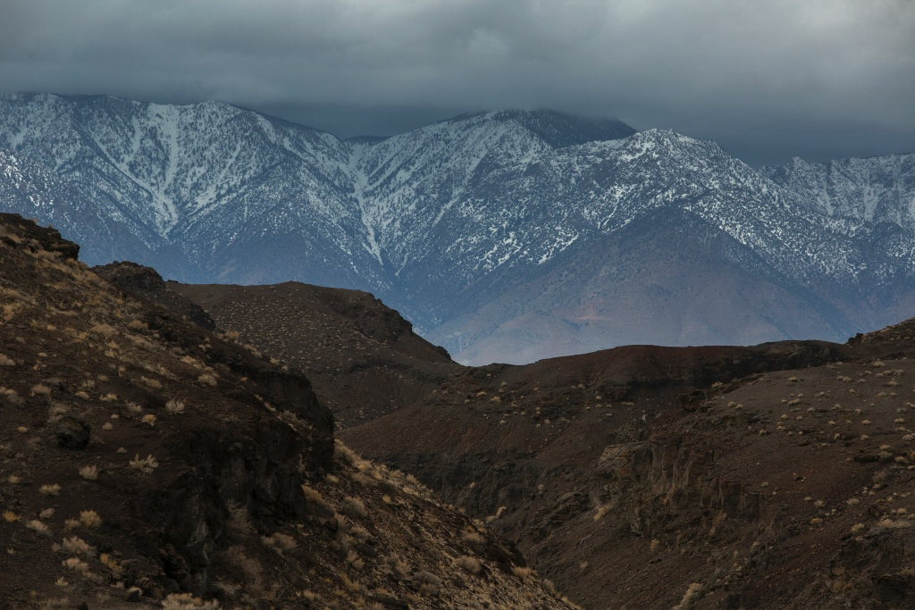 A volcanic desert landscape is seen with snowy Eastern Sierra Nevada Mountains in the distance near Lone Pine, California, January 8, 2017.
