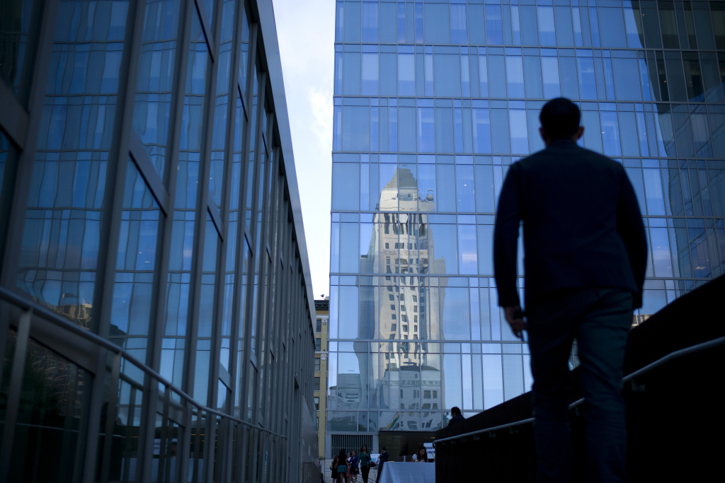 Los Angeles City Hall is reflected on the glass facade of the LAPD headquarters in this 2014 file photo. The city council voted unanimously Wednesday to move toward creating civilian panels that would review discipline involving cops accused of misconduct.