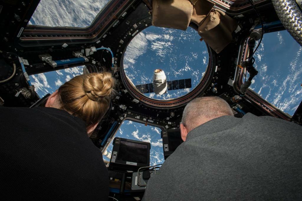 Astronauts on the International Space Station watch the SapceX Dragon capsule as it deploys.