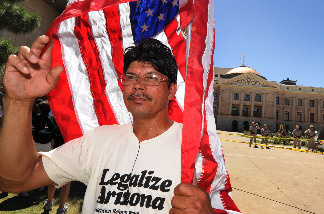 Alberto Gonzalez stands outside the Arizona State capital Building as he joins other protesters to demonstrate against Arizona's tough new immigration laws at a large rally in Phoenix on May 29, 2010.