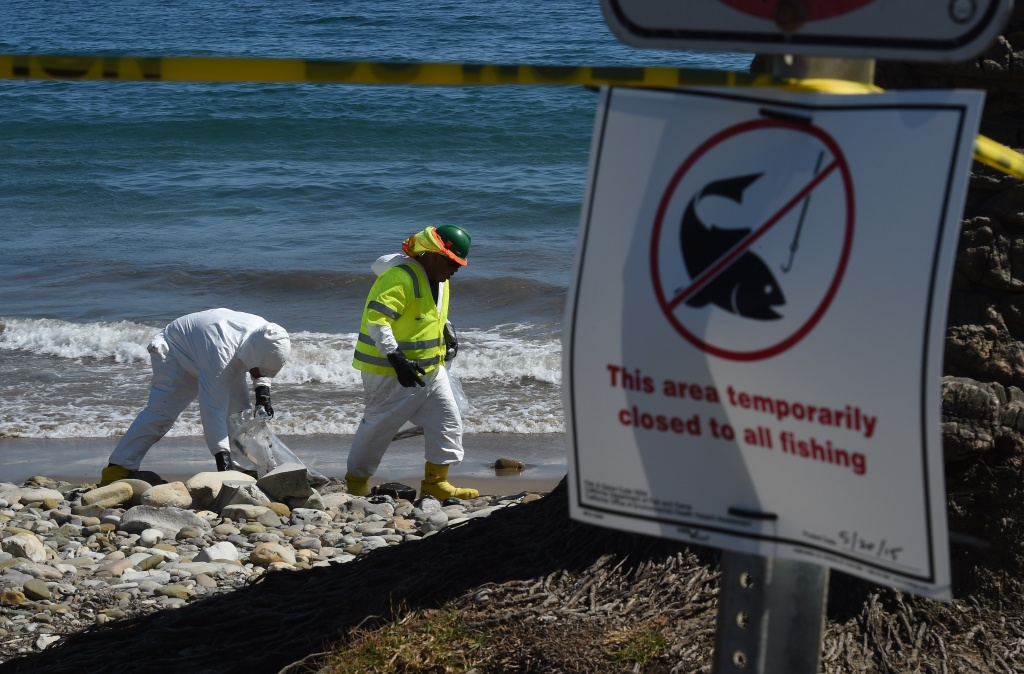Workers clean oil from the rocks and beach at Refugio State Beach in Goleta, California, May 22, 2015.