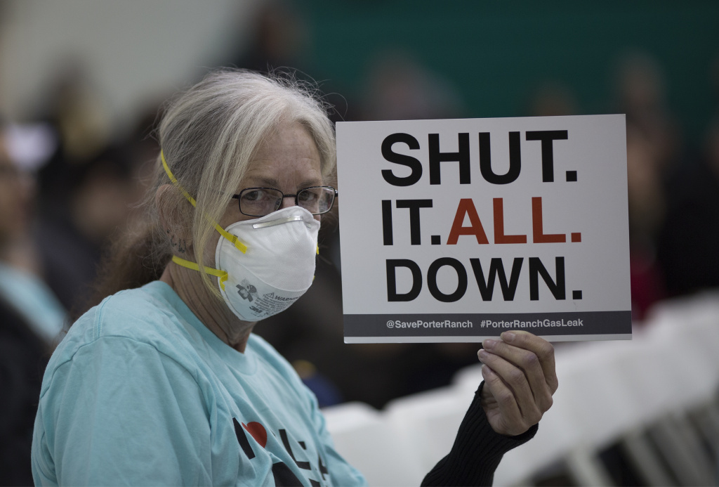 PORTER RANCH, CA - JANUARY 16:  A woman holds a sign while attending a public hearing before the South Coast Air Quality Management District (AQMD) about a proposed stipulated abatement order to stop a nearby massive natural gas leak.