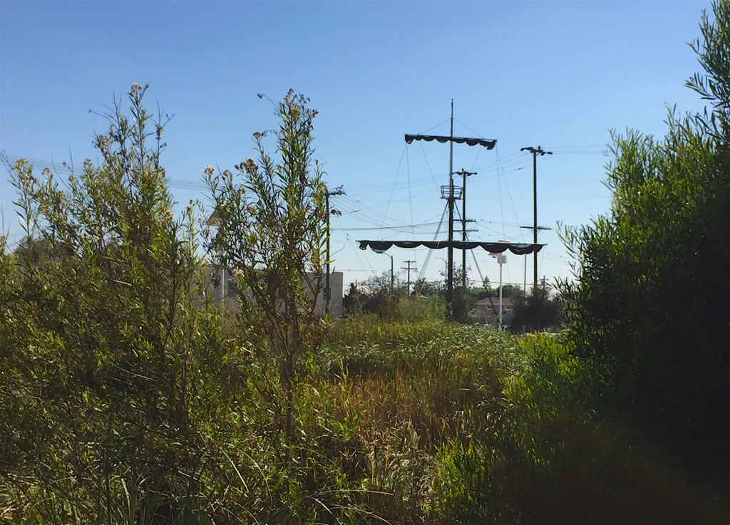 The sculpture, Mast, peeks through the greenery at the South LA Wetlands Park. Mast, which is made of a telephone pole, is part of the city's first-ever public art biennial, CURRENT:LA.