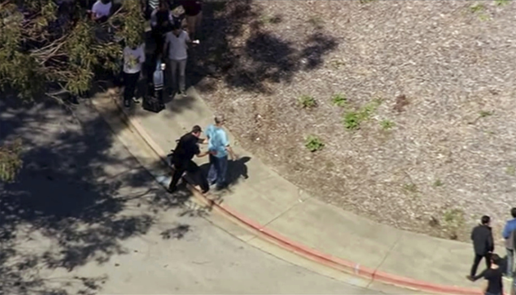 This image taken from video from KGO-TV shows a person is searched as police respond to reports of a shooting at YouTube headquarters in the city of San Bruno, Calif., on Tuesday, April 3, 2018. City Manager Connie Jackson says there have been multiple 911 calls reporting a shooting and that police and fire officials have responded.